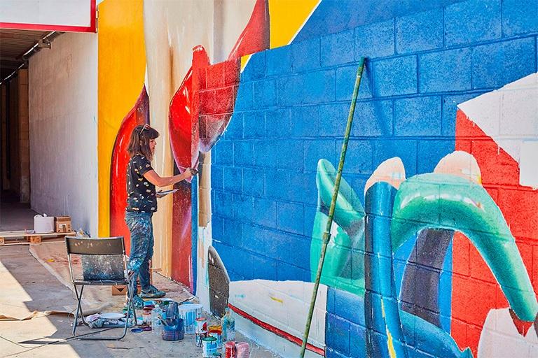 ana_barriga_pintando_mural_instalaciones_palibex_paleteria_transporte_urgente_mensajeria